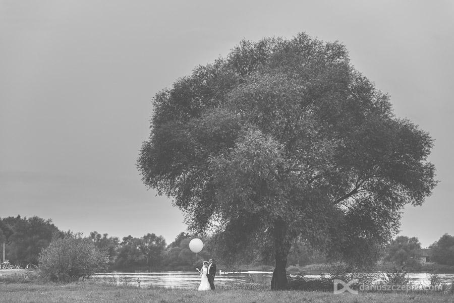 para młoda z balonem pod drzewem podczas sesji plenerowej w krakowie