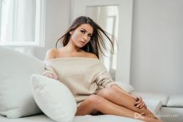 modelka na sofie w seksownym sweterku. Taki sweterek idealnie nadaje się zamiast bielizny do sesji kobiecej.