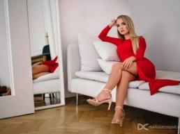 nierozbierana sesja kobieca z modelka pozujaca w czerwonej sukni w fotograficznym studio