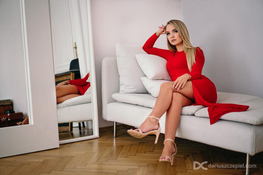 piękna blondynka pozuje w czerwonej sukience na sesji w studio art and more w Krakowie