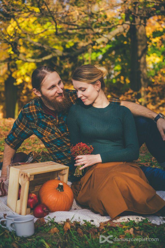 pionowy kadr zakochanej pary podczas jesiennej sesji narzeczeńskiej z rekwizytami i gadżetami