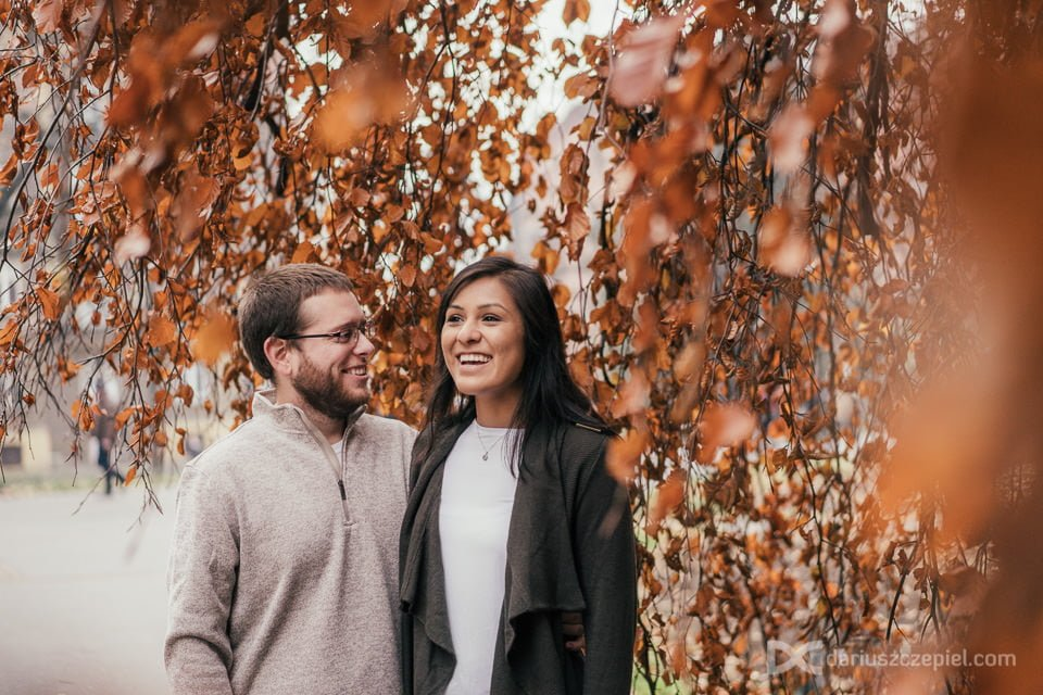 Couple posing in Krakow under a tree with colorful leaves in November