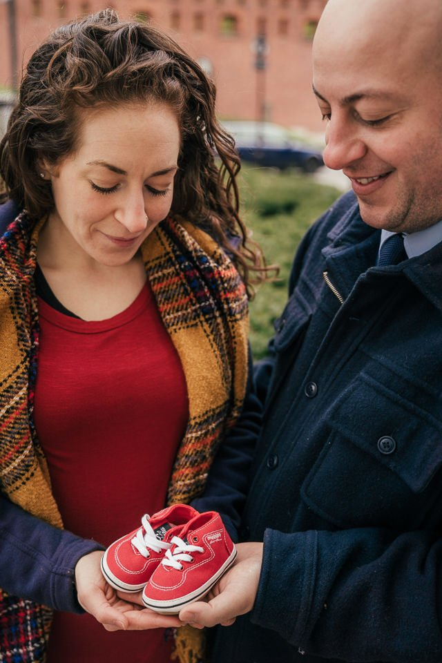A couple holding little shoes of thei unborn baby during a baby annoucement photosession done by a local Krakow photographer Dariusz Czepiel
