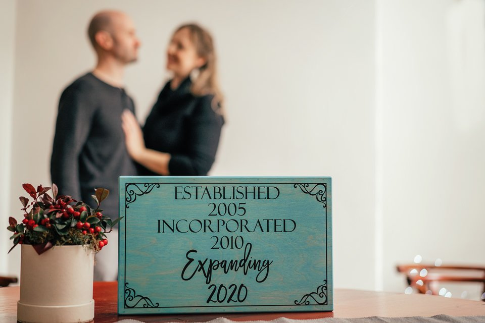baby annoucement photograph using a sign prepared by the pregnant couple shot by Dariusz Czepiel Fotografia a local Krakow lens